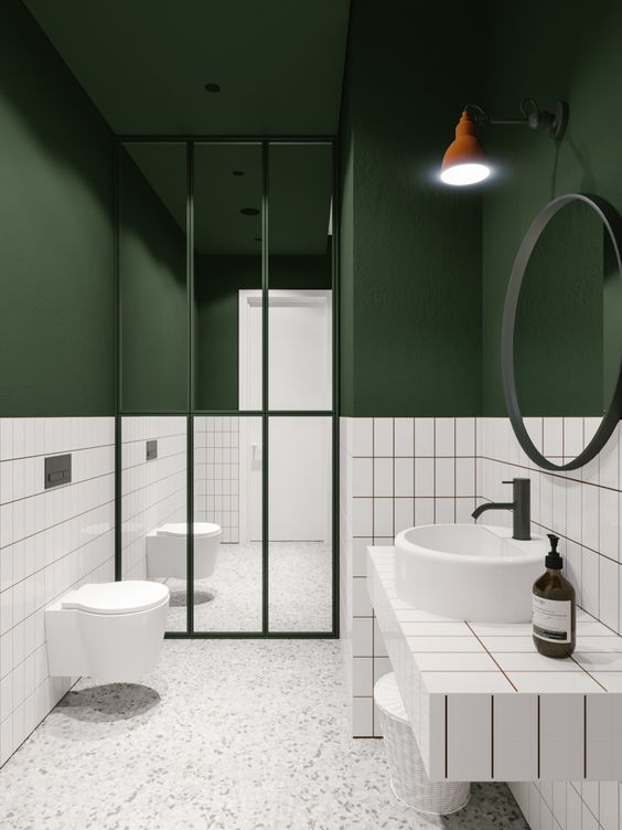 a bold modern bathroom with hunter green walls, white tiles and a stone floor plus white appliances
