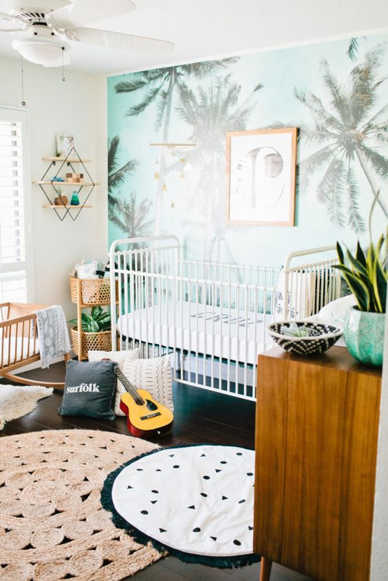 a bright and fun tropical nursery with palm print wall, potted plants, layered rugs and simple and neutral furniture