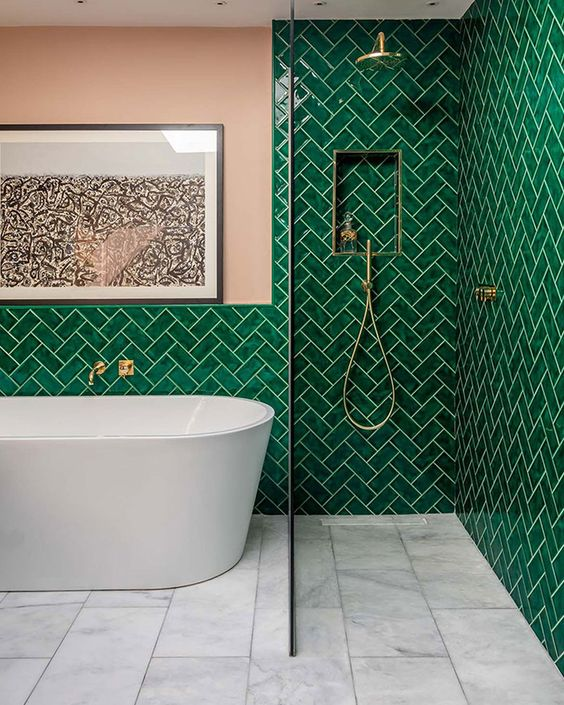 a bright bathroom with emerald tiles in a herringbone pattern, pink walls, gold touches and a white tub