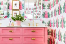 a bright bathroom with extra bold pineapple wallpaper walls, a bright pink vanity and potted greenery in a pink planter