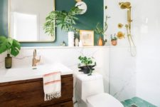 a bright ggreen bathroom with a green wall, a green mosaic tile floor, a wooden vanity and touches of gold and brass