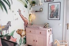 a bright tropical nursery with a pink changing table, a bright jungle print wall, bright artworks and a grey crib with a pink canopy