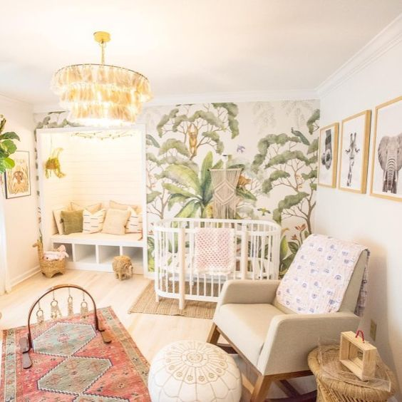 a bright tropical nursery with a tropical printed wall, a tassel chandelier, boho rugs, a leather ottoman and printed pillows