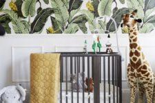 a bright tropical nursery with tropical leaf printed walls, a grey crib, animal toys and bright bedding
