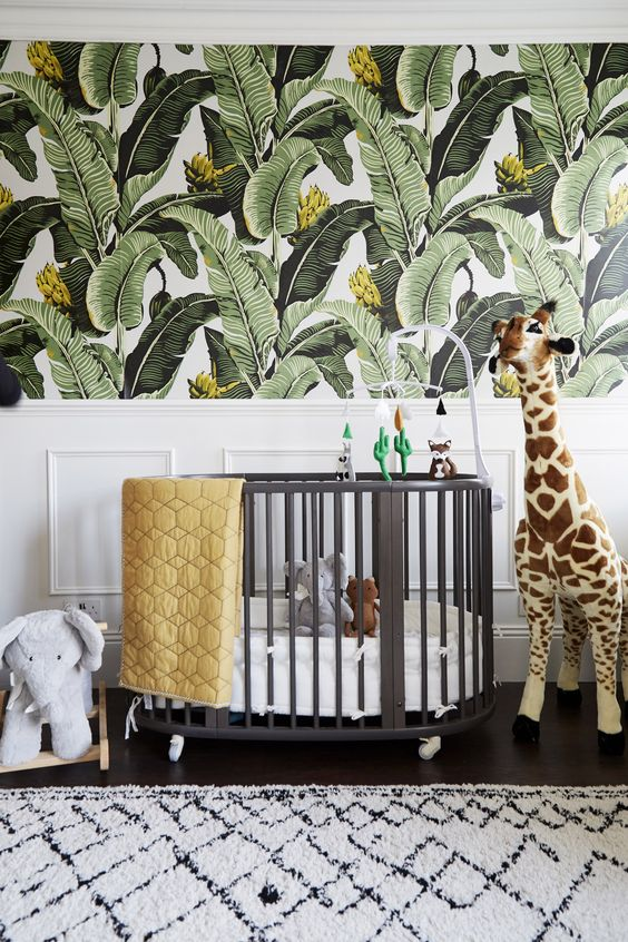 a bright tropical nursery with tropical leaf printed walls, a grey crib, animal toys and bright bedding