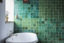 a catchy bathroom with a very special green tile wall in various shades, a vintage black tub and a mosaic floor