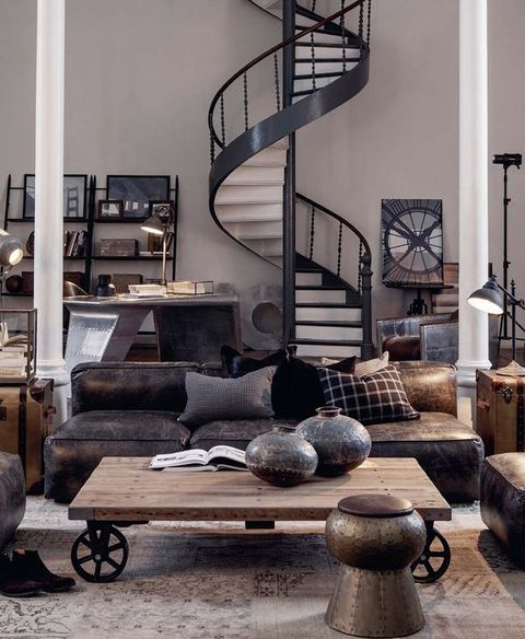 a catchy industrial living room with a leather sofa, metal and wood furniture that catches an eye and lamps here and there