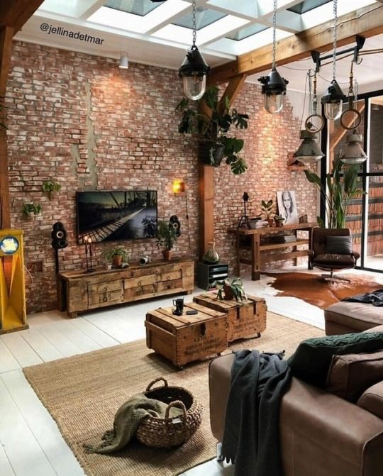 a catchy industrial living room with brick walls, a leather sofa and chair, pallet and crate furniture and cool pendant lamps
