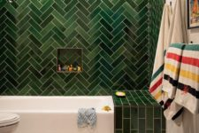 a catchy modern tub with green tiles clad in a herringbone pattern, a white tub and white tile floor