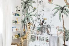 a cheerful jungle nursery with a fun printed statement wall, some shelves, cute toys and a bead chandelier