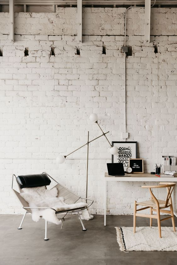 a chic and neutral home office with white brick walls that give a bold look to the space and catchy furniture