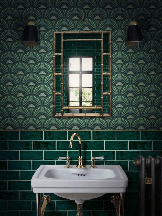 a chic art deco bathroom in green shades, done with tiles and wallpaper, with gold and brass touches looks awesome
