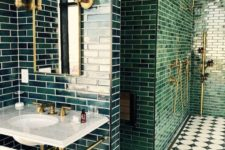 a chic art deco bathroom with dark green tiles, gold and brass touches, a stone vanity and black and white mosaic tiles
