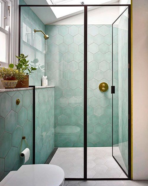 a chic bathroom with pale green hex tiles, a skylight, black framing is a catchy and contemporary space