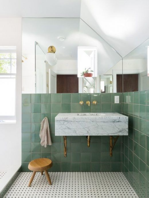 a chic bathroom with pale green tiles, mosaic tiles on the floor, a marble vanity and sink in one plus brass touches
