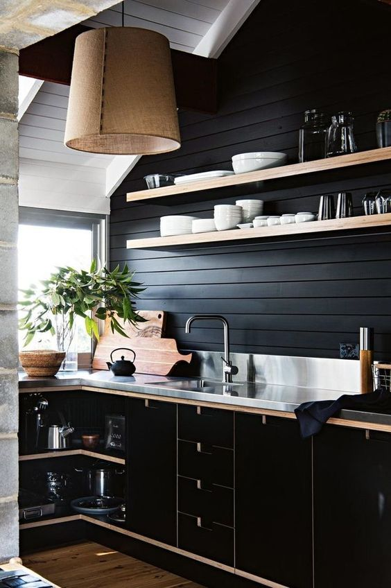 a chic black farmhouse kitchen with wooden planks, sleek black plywood cabinets and a metal countertop plus a burlap lamp