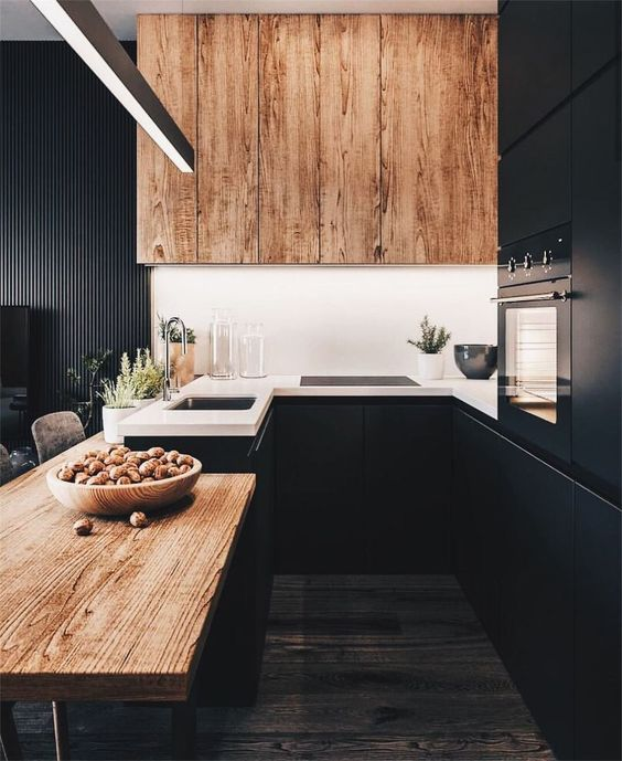 a chic black kitchen with a wooden table and a large hood plus white countertops looks very stylish and bold