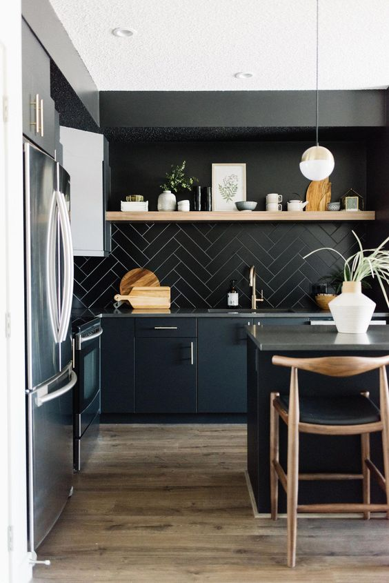 a chic black kitchen with black cabinets, a tile backsplash, concrete countertops and touches of light-colored wood