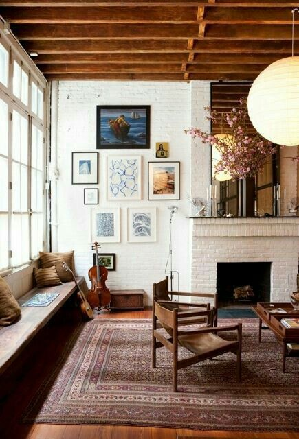 a chic farmhouse and vintage living room with a white brick wall and a white brick clad fireplace and a wooden ceiling
