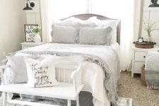 a chic farmhouse bedroom done in white, with vintage furniture, a sphere chandelier, baskets for storage and artworks