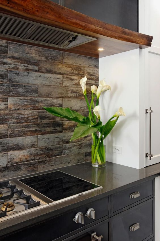 a chic farmhouse black kitchen with a wooden hood and wood tile backsplash plus sleek countertops looks wow