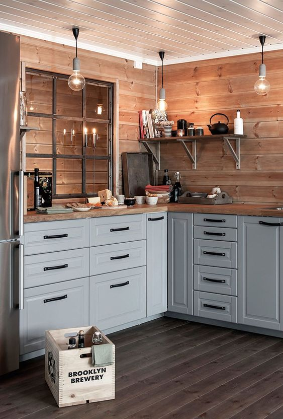 a chic farmhouse kitchen in grey, with wooden countertops and a backsplash plus touches of black looks very cozy