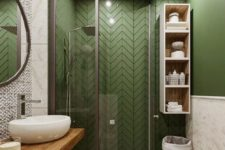 a chic grass green and neutral bathroom with printed tiles, a wooden vanity and a glass enclosed shower space