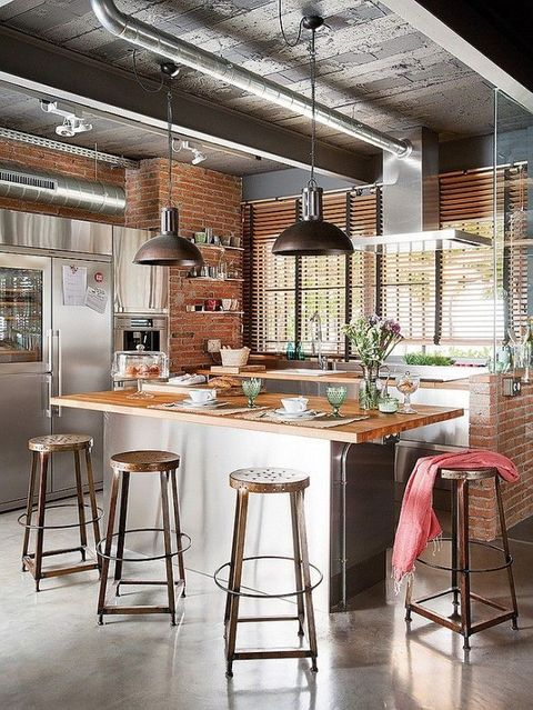 a chic industrial kitchen with red brick walls, metal cabinets and appliances, exposed pipes and metal stools
