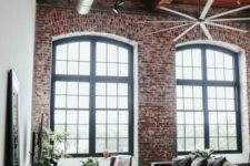 a chic industrial living room with brick walls, a wooden ceiling, exposed pipes, a metal chest, lots of greenery
