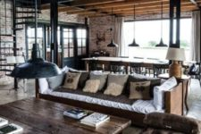 a chic industrial living room with brick walls, a wooden table, metal lamps and comfy wooden and upholstered furniture