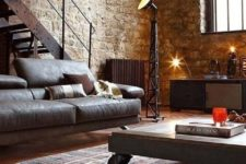 a chic industrial living room with stone walls, a leather sofa, a wood and metal table, a metal staircase and lamps here and there
