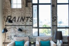 a chic industrial living room with white brick walls with stencils, a vintage chest, comfy furniture and metal lamps