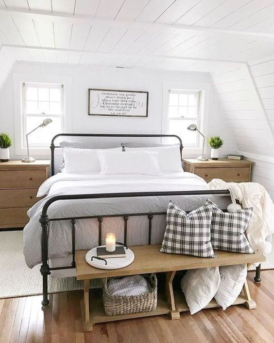 a chic modern farmhouse bedroom with white walls, a forged bed, wooden furniture and touches of plaid here and there
