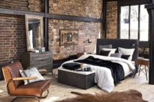a chic modern industrial bedroom with exposed metal, brick walls, upholstered furniture, a chest for storage and some animal skin rugs