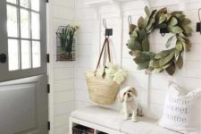 a chic neutral space with a leaf wreath, layered rugs, a built-in bench with baskets and some signs