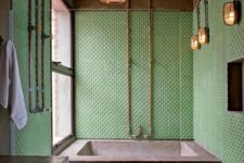 a colorful industrial bathroom with green polka dot tile walls, a concrete bathtub, exposed piping and vintage lamps