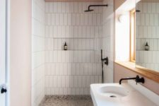 a contemporary bathroom with blush walls and a ceiling, white tiles and appliances and black fixtures