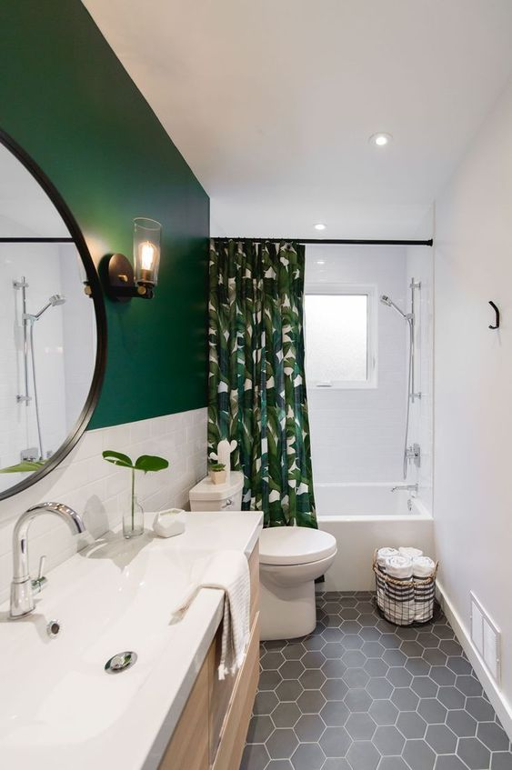 a contemporary bathroom with gray hex tiles, a green and white wall, a tropical print curtain and a large vanity