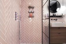 a contemporary bathroom with pink tiles clad in a herringbone pattern, with black touches and a wooden floating vanity