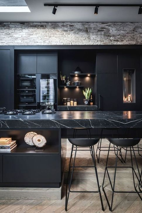 a contemporary black kitchen with a large kitchen island with a marble countertop, built-in lights and metal stools