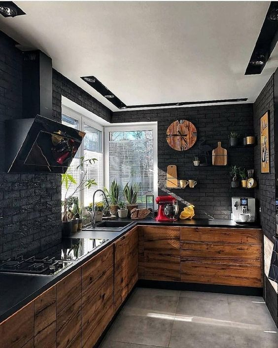 a contemporary black kitchen with black brick walls, light-colored wood cabinets, black countertops and a hood