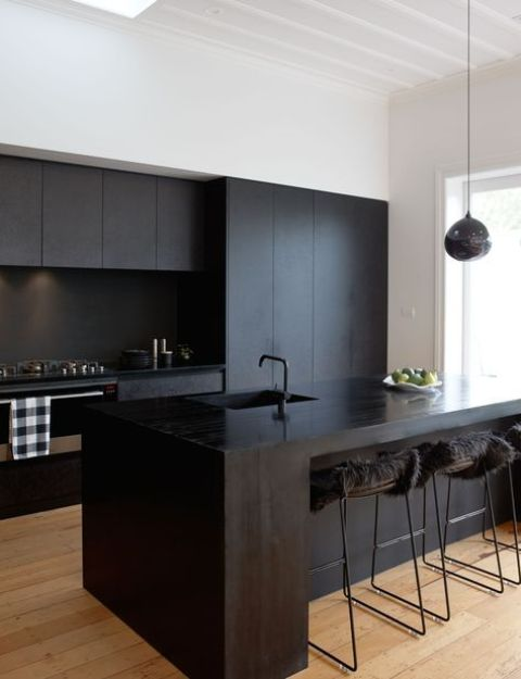 a contemporary black kitchen with sleek cabinets, a wooden kitchen island, stools with faux fur and a pendant lamp