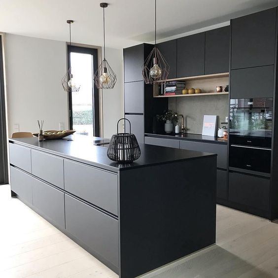 a contemporary black kitchen with sleek cabinets, an oversized kitchen island and catchy wire lamps
