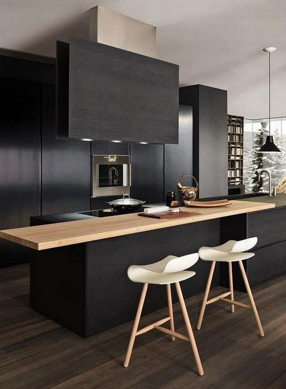 a contemporary black kitchen with sleek cabinets, built-in appliances, a light-colored wood countertop and a black hood