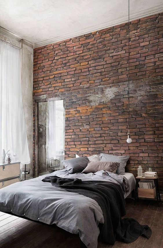a contemporary industrial bedroom with a faux red brick wall, a floating bed, nightstands, a mirror and pendant bulbs