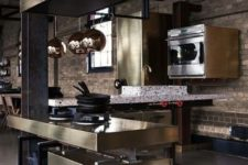 a contemporary industrial kitchen with brick walls, shiny metal cabinets and a hood, bright terrazzo ocuntertops and copper lamps