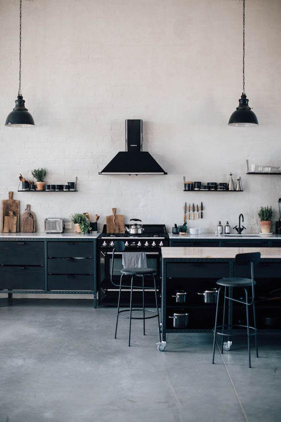 a contemporary industrial kitchen with metal wooden cabinets, white brick walls, vintage lamps and stools