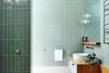 a contemporary light green bathroom clad with tiles, a floating wooden vanity and a round sink is chic