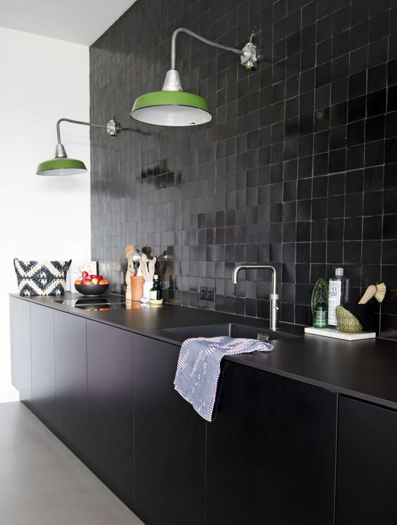 a cool black kitchen with sleek lower cabinets, tiles all over the wlal, green lamps and stone countertops