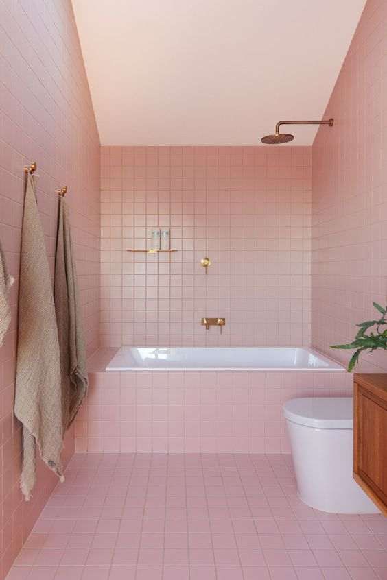 a cool contemporary pink bathroom with white appliancs and gold and copper fixtures plus potted greenery